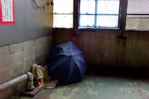 缩在墙角里睡觉的无家可归者,用雨伞隔出一片属于自己的空间.图片