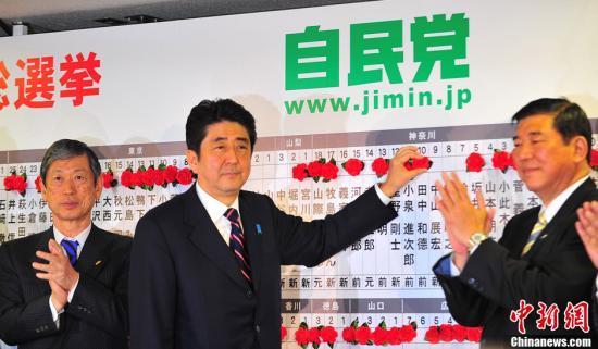 图为12月16日,自民党总裁安倍晋三(中)为当选议员贴获胜标志红花。中新社发 孙冉 摄