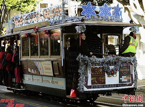 当地时间12月24日,圣诞节前夕,美国旧金山的人们乘坐装饰着圣诞饰品的有轨缆车快乐出行。中新社发 陈钢 摄