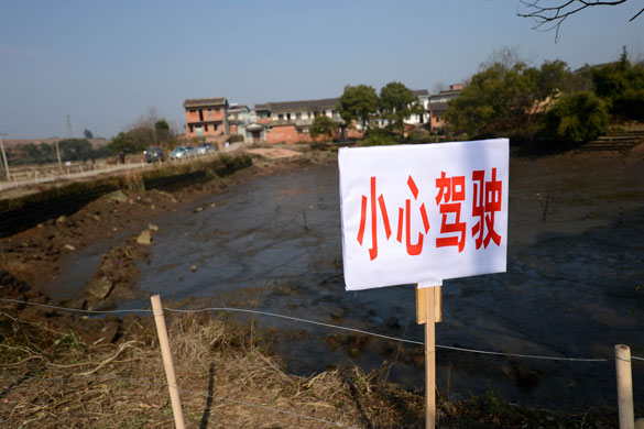 """贵溪市交通部门在事故现场设置了""""小心驾驶""""警示牌(2012年12月25日摄)。 摄影:新华社记者 周科"""