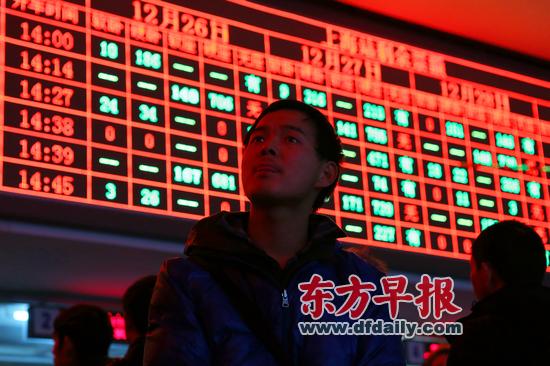 昨日,上海火车站,因12306铁路订票网站故障,很多市民只好选择到人工售票窗口购票或取票。早报记者 王辰 图