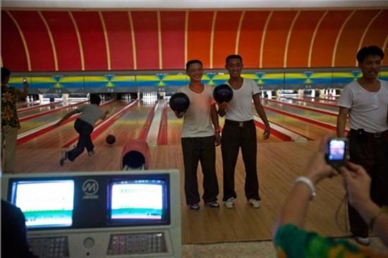 9月7日,平壤保龄球馆,两名男子手拿保龄球合影留念。