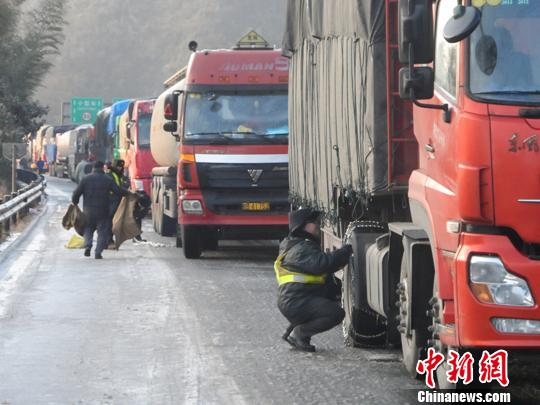 路政员为车辆安装防滑链。
