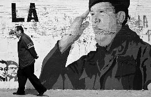 2012年12月30日,一名男子从委内瑞拉首都加拉加斯街头的查韦斯壁画旁走过。