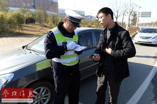 新交规2013年1月1日起实施,图为当天南昌一交警在给违章司机填写罚单。
