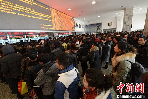"""1月7日,内蒙古呼和浩特火车站,售票厅的各个售票窗口前都排起""""长龙""""。中新社发 刘文华 摄"""