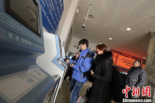 """1月7日,内蒙古呼和浩特火车站,售票厅的各个售票窗口前都排起""""长龙""""。图为通过互联网购票的人士,在自动取票机前取票。中新社发 刘文华 摄"""