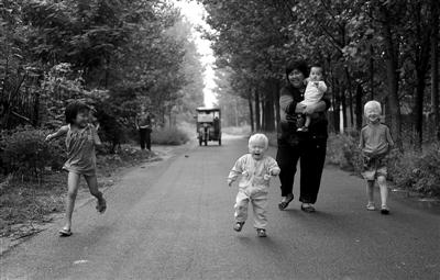 2011年9月7日,河南兰考县,袁厉害时常带着孩子到寄养的人家里相互串门。图/CFP