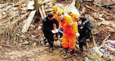 救援人员在救援现场搬运遇难者遗体 消防人员在山体滑坡事故现场救援。