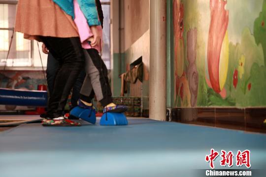 15日,在山西太原某自闭症康复机构,一名自闭症患儿正在进行肢体训练。 郭泽源 摄