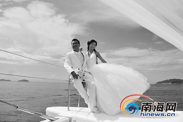 一对新人在游艇上以三亚亚龙湾碧海蓝天为背景拍摄婚纱.图片
