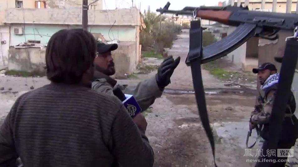 记者/图为该名记者身边的叙利亚叛军(中)接过同伴递过的武器,记者...