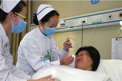 护士为苏丹整理胃管,苏丹强忍着难受的感觉。