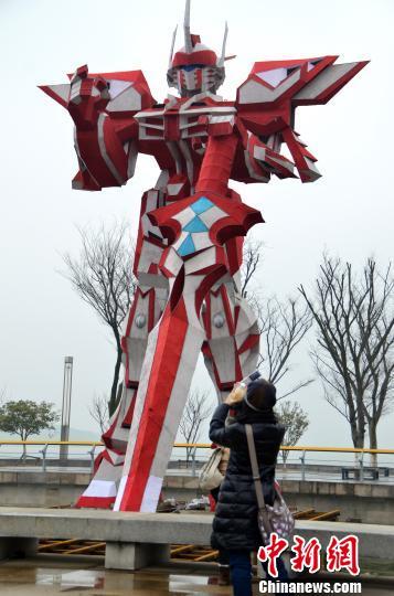 """1月21日,游客在巨型灯组""""变形金刚""""前拍照留念。该""""变形金刚""""灯组高12米,重达2.5吨,为目前世界最高的""""变形金刚""""灯组,在天空和湖水的映衬下显得格外高大神气。王思哲 摄"""
