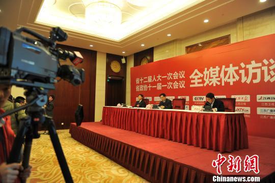 """1月21日晚,2013年江西省""""两会""""举行首场情况通报会,主席台上既没有鲜花,也没有绿色植物,非常简朴。 刘占昆 摄"""