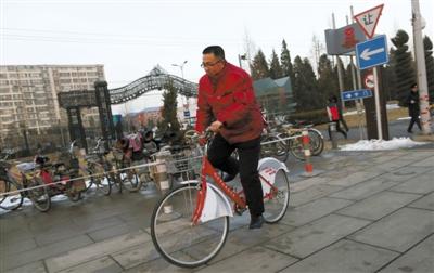 昨日,北京会议中心,市人大代表任素永骑着公租自行车来开会。新京报记者 薛�B 摄