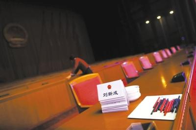 昨日,北京会议中心,服务员在会后整理主席台。今年两会,主席台上不摆设鲜花、绿植,桌上只有桌签、纸笔和茶杯。新京报记者 薛�B 摄