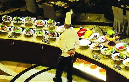 重庆一家五星级酒店的自助餐厅打烊前,厨师在查看当晚菜品剩余情况。 /新华社