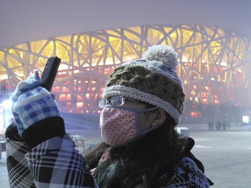 """1月22日傍晚,游客带着口罩在北京国家体育场""""鸟巢""""前拍照。新华社发(郭海鹏 摄)"""