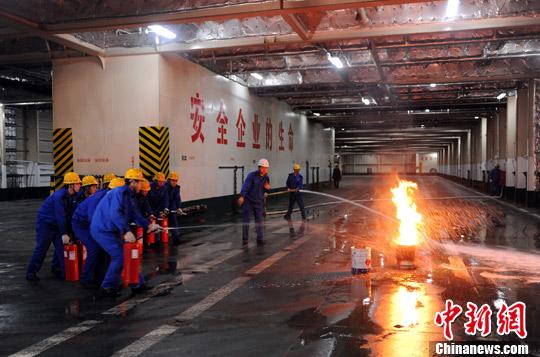 """23日,烟台海事部门在承担渤海湾运营任务的""""渤海玉珠""""号客滚船上举行消防救生应急演练。图为消防救生演练现场,船员准备进入模拟火灾现场探测火情。郝光亮 摄"""