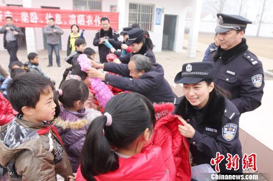 1月24日,南京铁路东站派出所民警和爱心网友在南京尧化流动人口学校为孩子们送上爱心棉衣 周春青 摄
