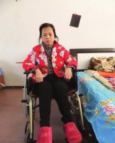 陈庆霞坐在轮椅上。她现在下身瘫痪,疾病缠身,生活不能自理。