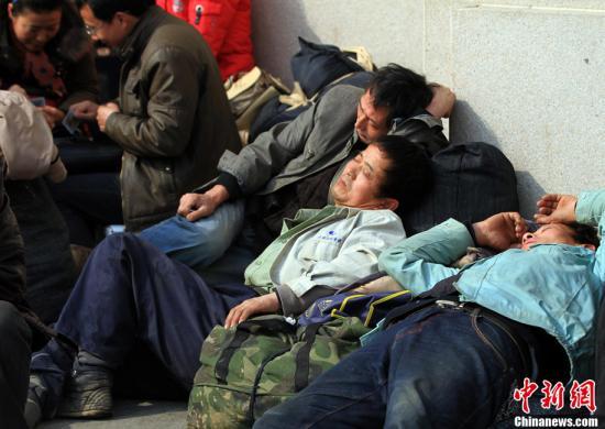 """1月26日,2013年春运拉开帷幕,作为全球最大的""""人口迁移"""",过年回家总能牵动众多中国人的心。图为汉口火车站站前广场等车的旅客由于疲惫睡着了。中新社发 张畅 摄"""