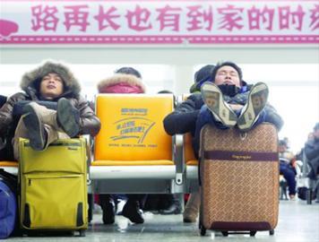 日前,在铁路虹桥站,两名外来务工人员正在等待回家的列车。