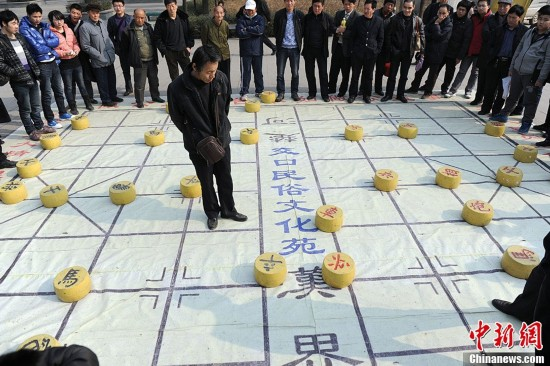 """28日,在西安市一公园内,一副巨大的象棋吸引了众多市民围观。不少棋迷上前""""手捧脚踢""""地对弈起来。图为棋迷对弈。张远 摄"""