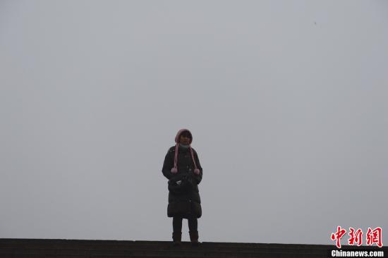1月29日晨,一名游客在北京天安门广场地区。当日北京雾霾天持续,空气严重污染。中新社发 刘震 摄