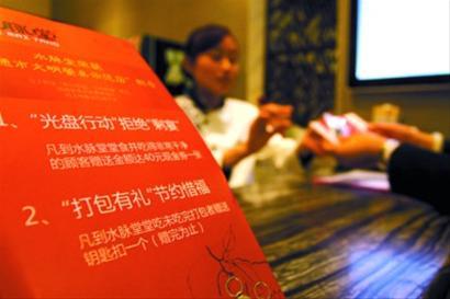1月26日,江苏省南通市一家饭店向打包剩菜的顾客赠送礼品 新华社发
