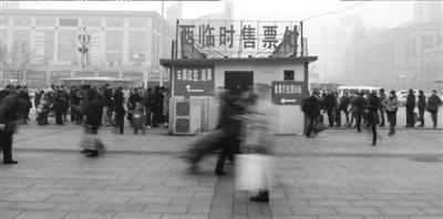 昨天下午,北京站广场上退票的人们在窗口前排起长队。本报实习记者赵思衡摄