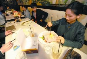 花城广场一家餐厅,一位市民将没吃完的食物打包。记者王燕 摄