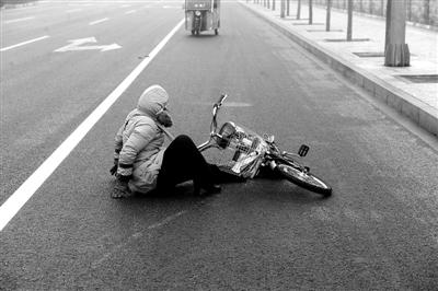 昨晨,阜通东大街,因道路湿滑一骑车女子不慎摔倒。马克 摄