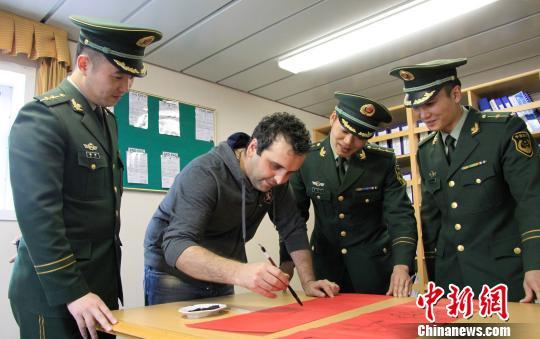 图为边检官兵和沙特籍外轮船员一同写对联。蒋振江 摄