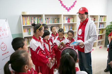 """2012年9月11日,""""小小图书室―台阁牧站""""濮存昕与孩子们在新的图书室里留下朗朗读书声。"""