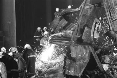 昨晚,消防战士正在破拆一辆摔碎的大卡车。昨日8时许,河南连霍高速三门峡段义昌大桥一侧垮塌,现已确认9死11伤。新京报记者 尹亚飞 摄