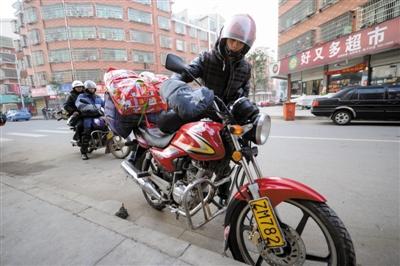 1月30日,赵雨兵(前)与几位老乡一起跨上摩托车,准备从浙江义乌骑摩托车回江西贵溪老家过年。新华社记者 鞠焕宗 摄