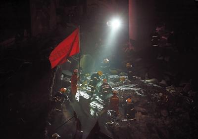 2月2日凌晨,消防战士在探照灯的照射下对废墟进行搜寻。
