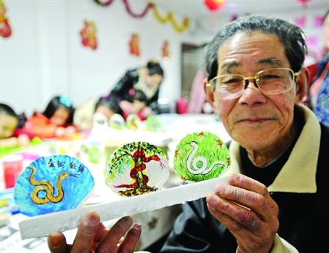 图为一名社区草根画家展示他在扇贝壳上画的彩蛇.记者杭兴微摄图片