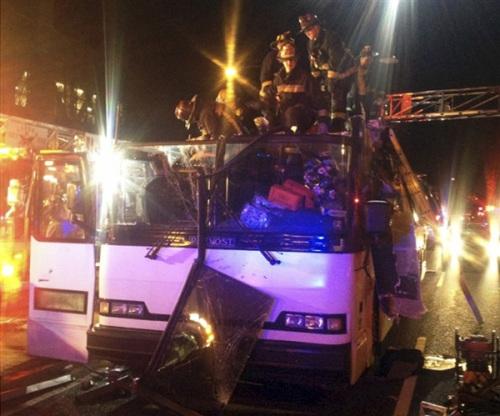 一辆大巴车在波士顿撞上立交桥,消防人员正从车内营救伤员。