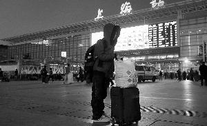 1月28日,上海火车站,15岁的何杰独自一人站在南广场等待去取票的爸爸,准备赶回老家兰州。 早报记者 王辰 图