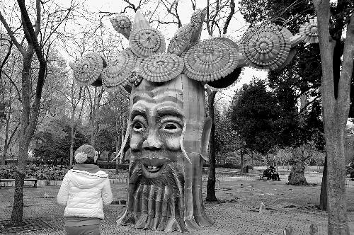 欣赏 郑州/2月5日,游人在郑州市人民公园内欣赏一个由废旧塑料瓶做装饰的...