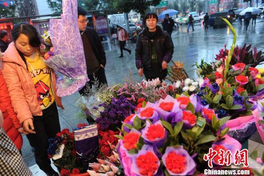 2月7日,四川省达州市一家鲜花店店员正在为顾客选购鲜花.