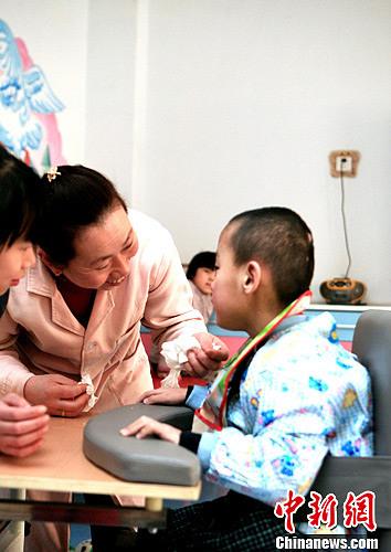 2月8日,石家庄福利院工作人员正在给患脑瘫的弃婴擦鼻涕。李光 摄