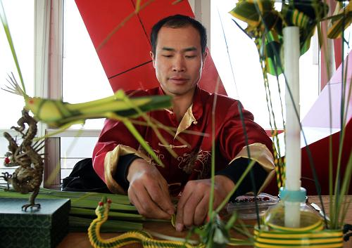 2月10日,一位民俗艺术家在制作草编工艺品.新华社发(丁汀 摄)