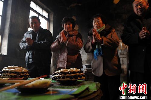 """2月10日大年初一,中国河北献县垒头村一村户家,村民在锅灶边供奉上自制的贡品,以祭拜""""灶神""""祈求来年五谷丰登。灶神,也称灶王,中国古代神话传说中的司饮食之神。中新社发 翟羽佳 摄"""