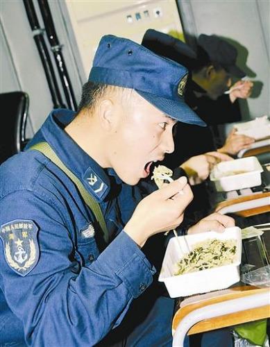 """""""青岛""""舰上的官兵在战位上吃野战快餐。图片来源:解放军报记者 米晋国"""