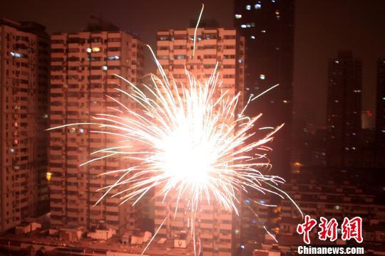 图为正月初五零时,在南京新街口地区的楼宇间,许多市民正在燃放烟花炮竹。 卢辉 摄