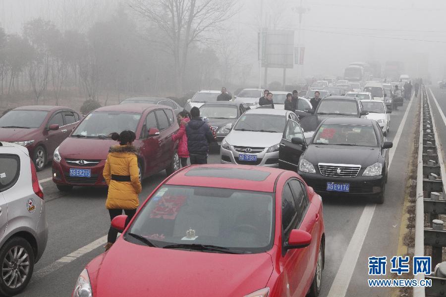 江苏/2月14日,同三高速江苏赣榆入口处因大雾封闭,旅客下车等待。